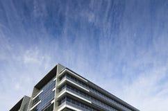 现代玻璃大厦在剧烈的天空下 免版税图库摄影