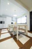一个现代豪华明亮的白色厨房的内部有用餐的选项 库存图片