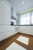 一个现代豪华明亮的白色厨房的内部 图库摄影