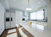 一个现代豪华明亮的白色厨房的内部 免版税库存图片