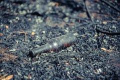 一个玻璃啤酒瓶在被烧焦的地面上说谎 库存照片