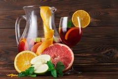 一个玻璃水罐与切片的饮料苹果和桔子、葡萄柚和薄菏绿色叶子在木背景的 免版税库存图片