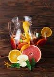 一个玻璃水罐与切片的饮料苹果和桔子、葡萄柚和薄菏绿色叶子在木背景的 免版税库存照片