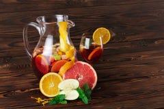 一个玻璃水罐与切片的饮料苹果和桔子、葡萄柚和薄菏绿色叶子在木背景的 免版税图库摄影