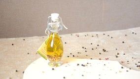 一个玻璃瓶子有橄榄油和香料的和洒用在桌上的胡椒 股票视频