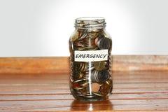 一个玻璃瓶子硬币充分代表紧急状态 库存图片