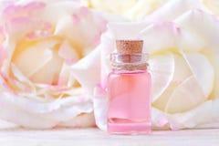 一个玻璃瓶精油和新鲜的玫瑰色花,选择聚焦 免版税图库摄影