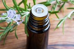 一个瓶与开花的迷迭香枝杈的迷迭香精油 图库摄影