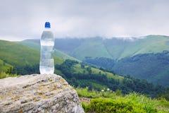 一个瓶在塑料瓶的纯净的饮用水在山 库存照片
