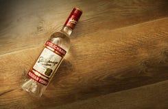 一个瓶在木背景的Stolichnaya伏特加酒 免版税图库摄影