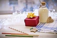 一个瓶奶油和一件礼物在tabler 免版税库存图片