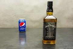 一个瓶威士忌酒-杰克丹尼尔` s 百事可乐在背景中能 免版税库存图片