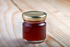 一个瓶子在一张木桌上的褐红的果酱 库存照片
