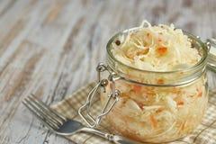 一个瓶子德国泡菜和红萝卜在它自己的汁液用香料在光,白色木桌,一垂直的圆白菜在瓶子 免版税库存图片