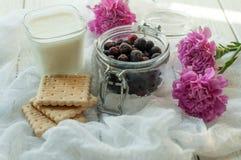 一个瓶子新鲜的莓果、一杯自创酸奶,饼干和明亮的紫色花精美白色织品表面上  免版税库存照片