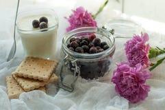 一个瓶子新鲜的莓果、一杯自创酸奶,饼干和明亮的紫色花精美白色织品表面上  免版税库存图片