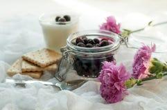 一个瓶子新鲜的莓果、一杯自创酸奶,饼干和明亮的紫色花精美白色织品表面上  库存照片