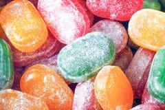 一个瓶子明亮的糖果 孩子,很多甜点喜悦  糖果被分类的颜色 在搽粉的糖的焦糖 免版税库存图片