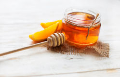 一个瓶子蜂蜜和桔子在白色木表上 库存图片