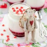 一个瓶子酸奶用山莓果酱和玩具熊玩具倾斜 库存照片