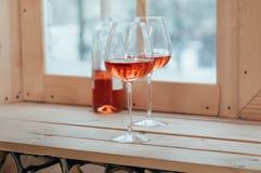 一个瓶玫瑰酒红色和两填装了在窗口基石的玻璃 免版税库存照片