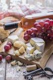 一个瓶玫瑰酒红色,葡萄,乳酪,黄柏,拔塞螺旋,白面包服务与在白色背景的一块纺织品毛巾 库存照片