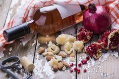一个瓶玫瑰酒红色, pomergranate,乳酪,黄柏,拔塞螺旋,白面包服务与在老白色的一块纺织品毛巾 库存照片