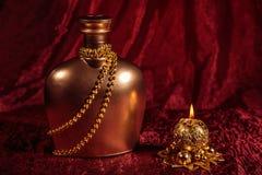 一个瓶白兰地酒和在红色背景的蜡烛在新年和圣诞节 免版税库存照片