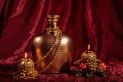 一个瓶白兰地酒和蜡烛在新年和圣诞节在红色背景 免版税库存照片