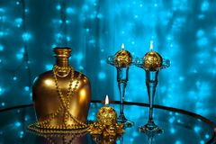 一个瓶白兰地酒和蜡烛在新年和圣诞节在蓝色背景 库存图片