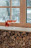 一个瓶的一个垂直的图象酒和玻璃在窗口sil 免版税图库摄影