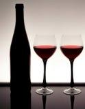 一个瓶的剪影与两块玻璃的酒用酒 库存照片