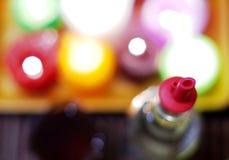 一个瓶的抽象图象与塑料pourer和迷离colorfull的酒对光检查背景 库存图片