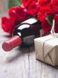 一个瓶红葡萄酒,礼物,英国兰开斯特家族族徽花束在土气老葡萄酒背景的 免版税图库摄影