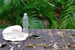 一个瓶饮用水、帽子和手机在木桌上有绿色自然背景 免版税库存照片