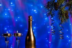 一个瓶香槟和蜡烛在与圣诞树的新年分支 免版税库存照片