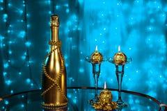 一个瓶香槟和蜡烛在新年和圣诞节在蓝色背景 库存图片