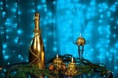 一个瓶香槟和蜡烛在新年和圣诞节在蓝色背景 免版税库存照片
