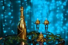 一个瓶香槟和蜡烛在新年和圣诞节在蓝色背景 免版税库存图片