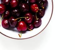一个甜樱桃的莓果与水滴的在白色背景的一个碗 库存照片