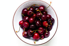 一个甜樱桃的莓果与水滴的在白色背景的一个碗 免版税库存照片