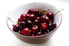 一个甜樱桃的莓果与水滴的在白色背景的一个碗 库存图片