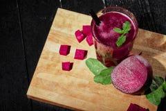 一个甜菜饮料的顶视图在玻璃的 削减红色甜菜根和绿色在黑桌背景 健康圆滑的人 免版税库存图片