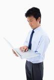 一个生意人的纵向使用膝上型计算机的 免版税库存照片