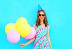 一个生日盖帽的愉快的俏丽的微笑的少妇有在蓝色背景的空气五颜六色的气球的 图库摄影