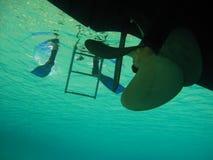 一个电动机转速的小船电动子的刀片,在船下 图库摄影