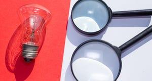 一个电灯泡和放大镜在分开的红色和白色 免版税图库摄影