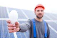 一个电灯泡在一名雇员的手上在焦点在太阳电池板被弄脏的背景  库存照片