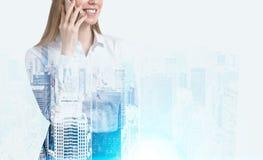一个电话的妇女在一个有雾的城市 免版税库存图片