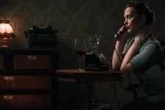 一个电话的美丽的少妇在减速火箭的内部 免版税库存照片